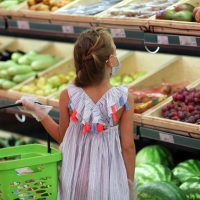 A girl in a medical mask in a supermarket buys vegetables and fruits. Social distancing, purchasing food safely COVID - 19 .